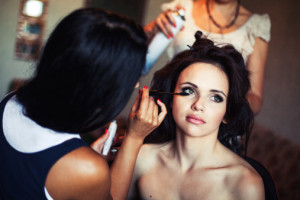 wedding. Young beautiful girl applying make-up by artist